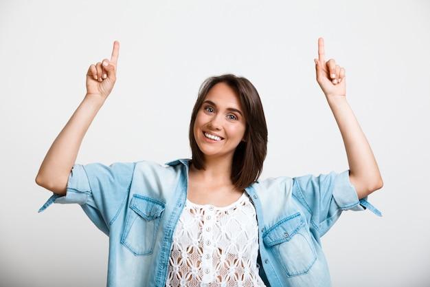 Jovem mulher entusiasta apontando para cima