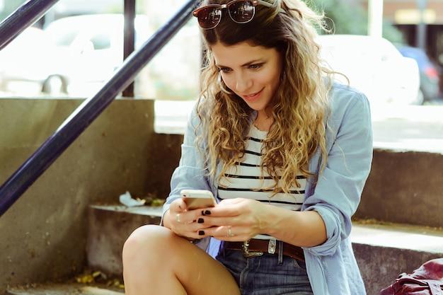 Jovem mulher enviando mensagem com o smartphone.