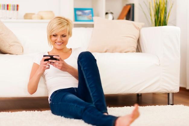 Jovem mulher enviando mensagens de texto em casa
