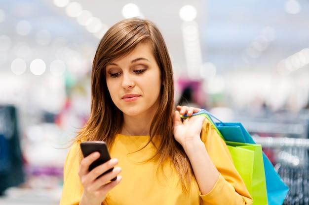 Jovem mulher enviando mensagens de texto no celular na loja