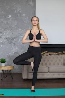 Jovem mulher envolvida em casa de ioga, mulher em pose de árvore