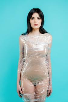 Jovem mulher envolvida em tampa plástica de polietileno. resíduos não degradáveis e conceito de poluição