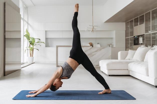 Jovem mulher equilibrada em roupas esportivas, fazendo uma pose de ioga com um golfinho de pernas no tapete em casa, na sala de estar, praticando ioga