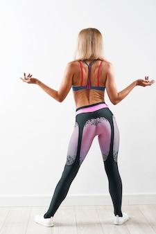 Jovem mulher esbelta no sportswear mostrou seu corpo musculoso atlético tonificado
