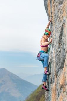 Jovem mulher escadas uma parede durante um curso de rock