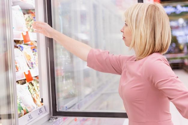Jovem mulher escolhe alimentos congelados em um supermercado.