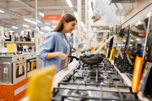 Jovem mulher escolhendo fogão a gás na loja de eletrônicos. mulher comprando eletrodomésticos no mercado, dona de casa procurando mercadorias na loja