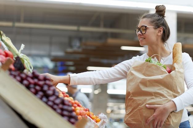 Jovem mulher escolhendo frutas Foto Premium