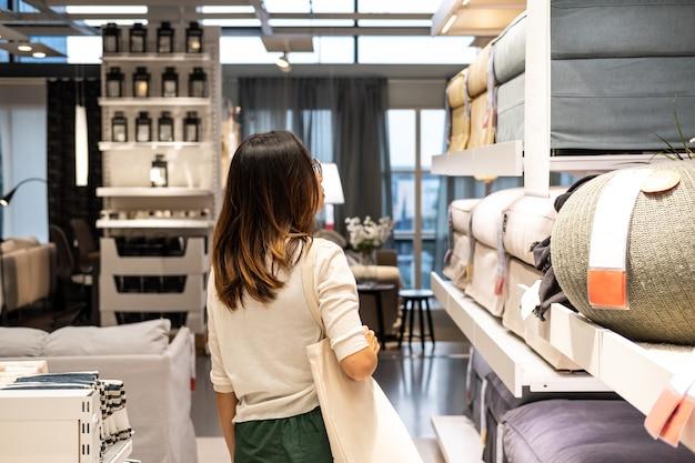 Jovem mulher escolhendo móveis em uma loja de móveis para casa moderna