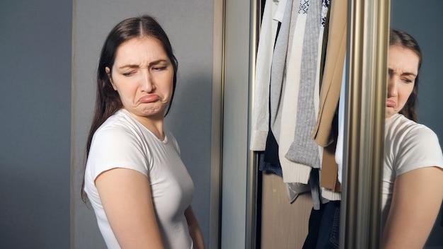 Jovem mulher escolhendo roupas no guarda-roupa em casa. conceito de nada para vestir