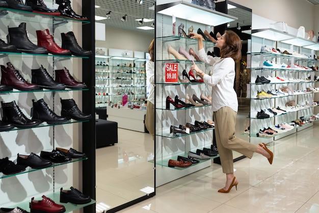 Jovem mulher escolhendo sapatos glamour, dobrando a perna