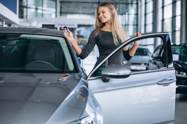 Jovem mulher escolhendo um carro em uma sala de exposições
