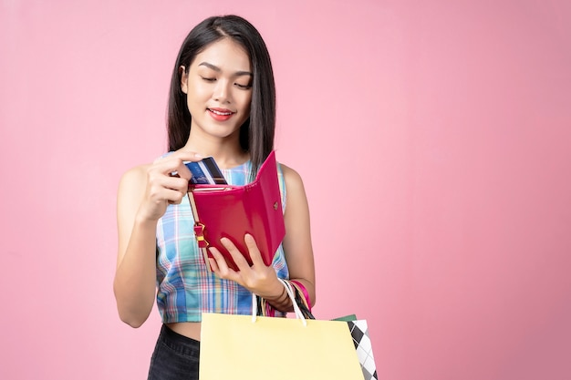 Jovem mulher escolhendo um cartão de crédito da bolsa com um sorriso e carregando sacolas de compras,