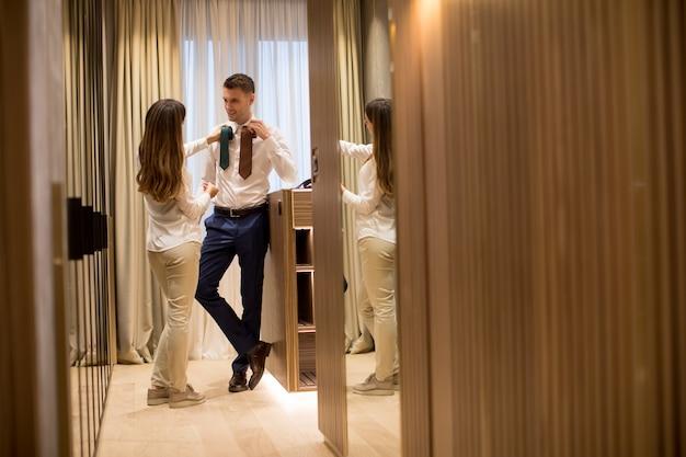Jovem mulher escolhendo uma gravata para seu marido bonito