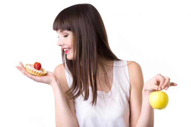 Jovem, mulher, escolher, bolo, em vez de, maçã