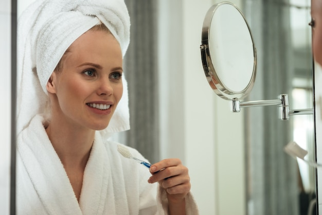 Jovem mulher escovando os dentes contra o espelho