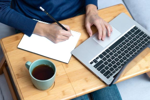 Jovem mulher escrevendo a lápis na mesa de madeira com laptop e uma xícara de chá.