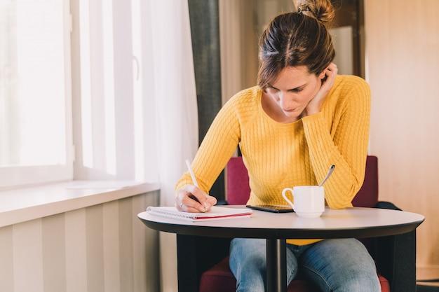 Jovem mulher escrevendo em um caderno enquanto trabalhava em casa. conceito de trabalho ou estudo em casa.