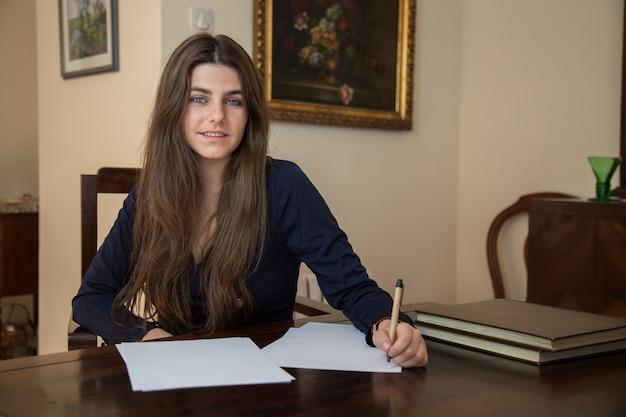 Jovem mulher escrevendo em uma folha em branco com uma caneta.
