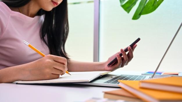 Jovem mulher escrevendo no papel de caderno e lendo na tela do smartphone.