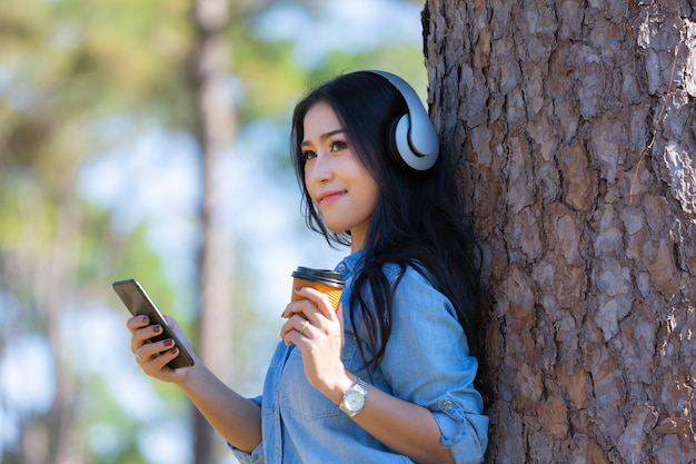 Jovem, mulher, escutar música, em, modernos, fones, comunicar-se, online, com, xícara café