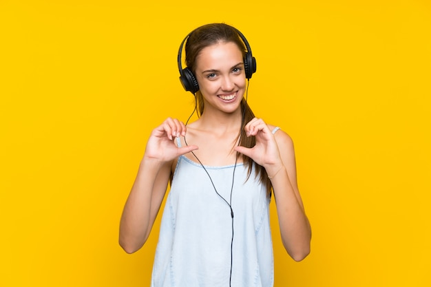 Jovem, mulher, escutar, música, sobre, isolado, parede amarela, orgulhoso, e, self-satisfied