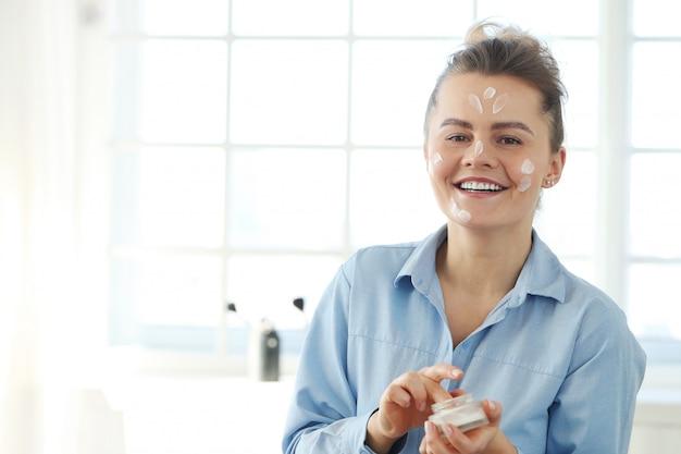 Jovem mulher espalhando creme facial. conceito de cuidados com a pele.
