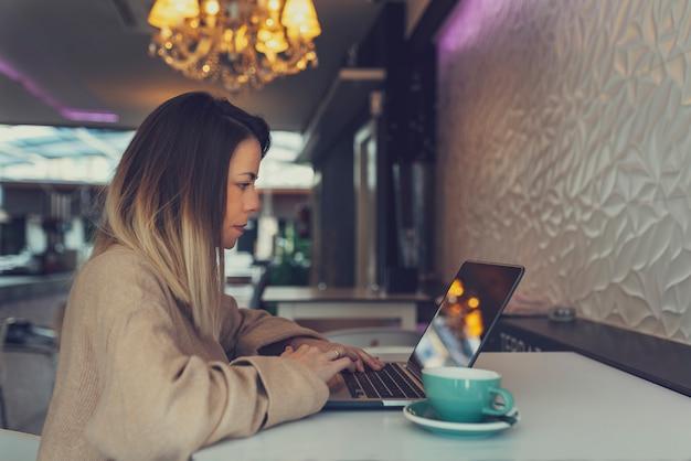Jovem mulher espanhola usando seu laptop na cafeteria de paredes brancas enquanto bebia café