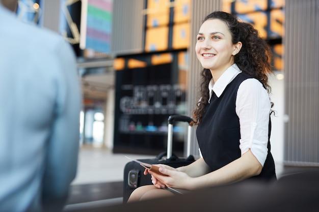 Jovem mulher esperando no aeroporto a sorrir