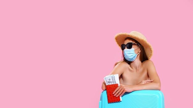 Jovem mulher esperando o voo sentada no chão perto de sua mala, usando máscara facial para evitar coron
