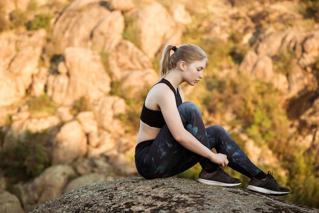 Jovem mulher esportiva amarrar cadarços, sentado na pedra no canyon