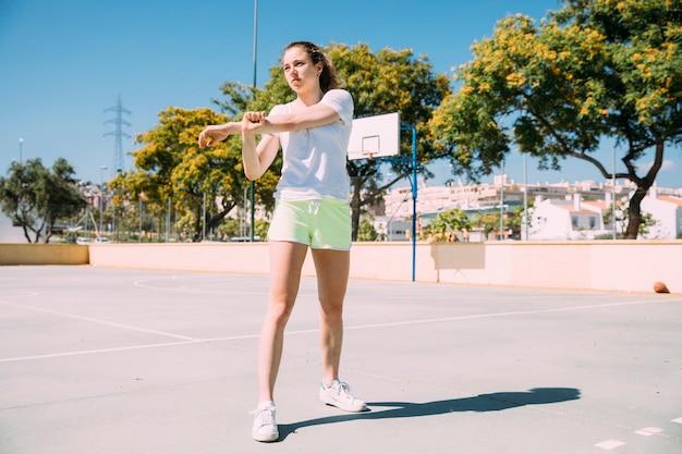 Jovem mulher esportiva aquecendo os braços