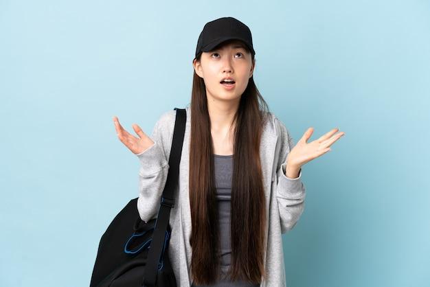 Jovem mulher esportiva chinesa com bolsa esportiva isolada