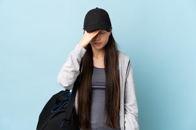 Jovem mulher esportiva chinesa com bolsa esportiva sobre azul isolado com dor de cabeça