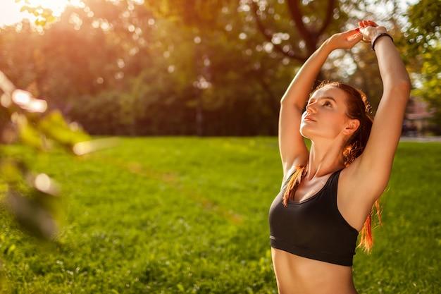 Jovem mulher esportiva fazendo pose de ioga no parque de verão.