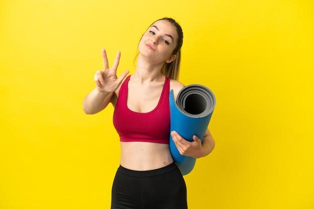 Jovem mulher esportiva indo para aulas de ioga, segurando um tapete feliz e contando três com os dedos