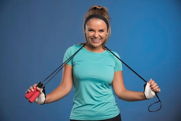 Jovem mulher esportiva pendurando cordas de pular em seu pescoço e sorrindo.