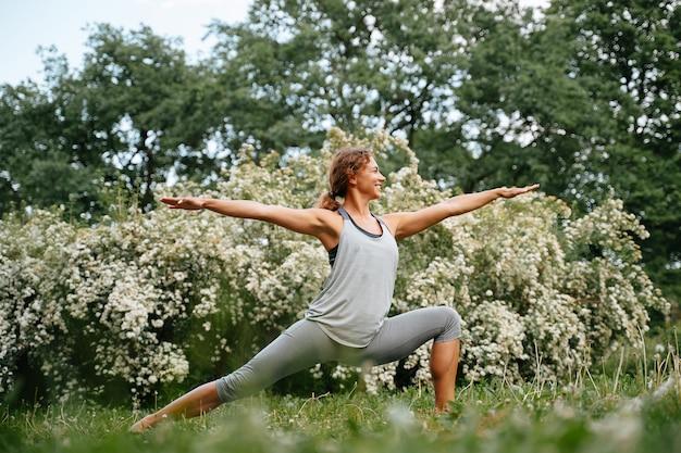 Jovem mulher esportiva praticando ioga fazendo pose de guerra ao ar livre atividades esportivas para alongar as pernas na horizontal
