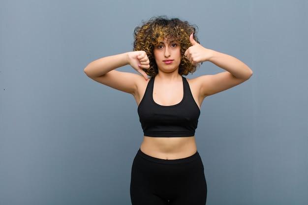 Jovem mulher esportiva se sentindo confusa, sem noção e insegura, pesando o que é bom e o que é ruim em diferentes opções ou escolhas na parede cinza