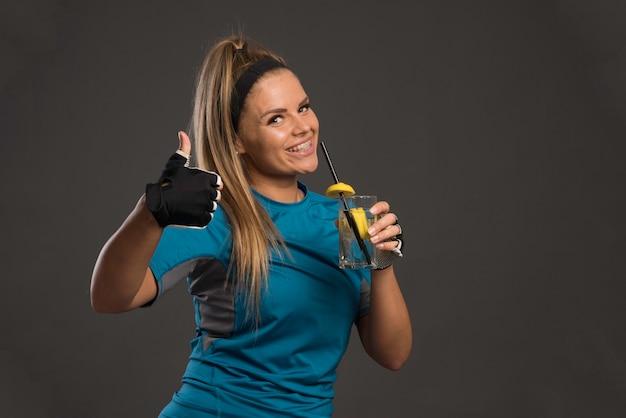 Jovem mulher esportiva tomando uma bebida energética e o polegar para cima.