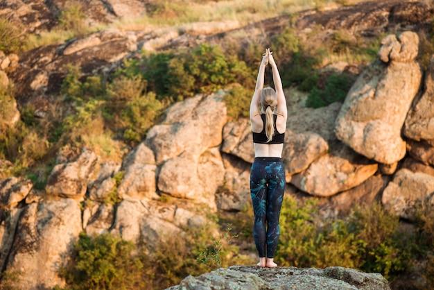 Jovem mulher esportiva treinamento yoga asanas na rocha no canyon