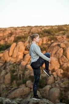 Jovem mulher esportiva treinando, sctretching na rocha no canyon