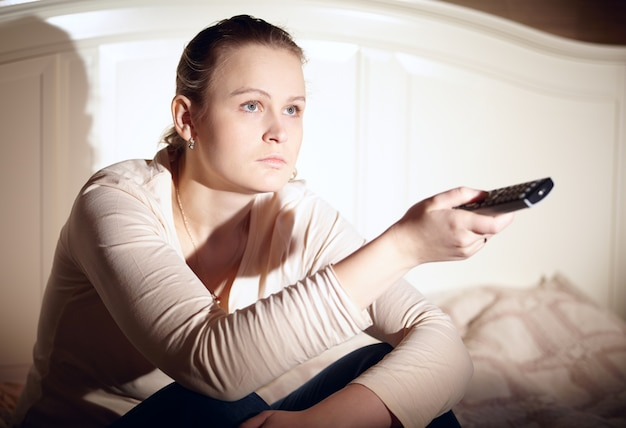 Jovem mulher está assistindo tv.