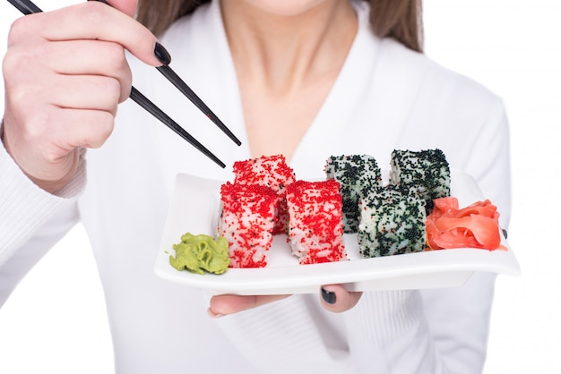 Jovem mulher está comendo sushi com um pauzinho.