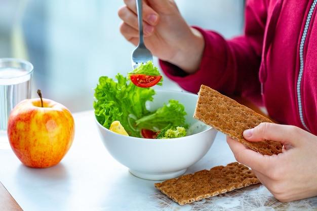 Jovem mulher está comendo uma salada saudável, fresca e vegetal com pão de centeio. dieta e conceito de estilo de vida saudável. dieta alimentar. nutrição adequada e comer direito