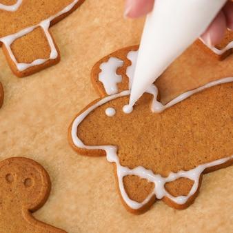 Jovem mulher está decorando biscoito de biscoitos de casa de gengibre de natal em casa com cobertura de cobertura no saco de confeiteiro, close-up, estilo de vida.