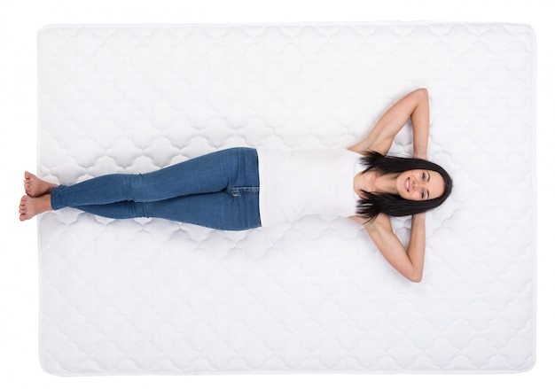 Jovem mulher está deitada na cama branca.