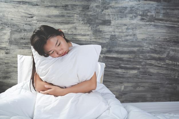 Jovem mulher está deprimida em uma cama branca