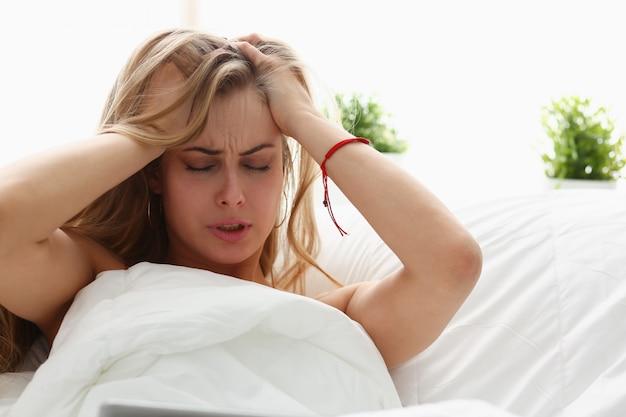 Jovem mulher está doente ficar na cama tem um headacke