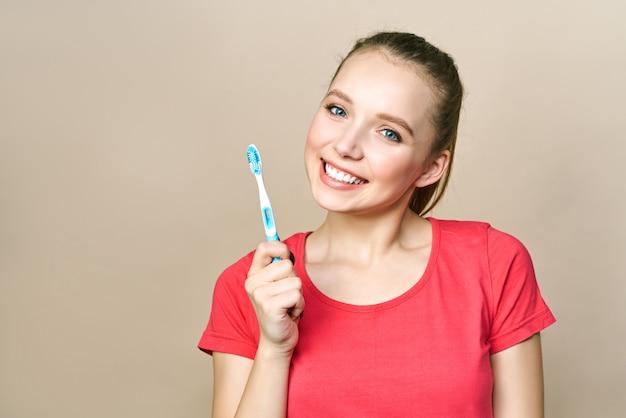 Jovem mulher está envolvida na limpeza dos dentes